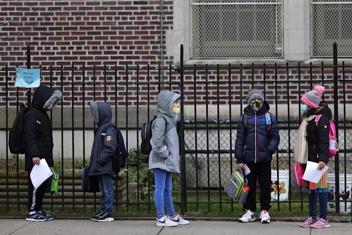 Children returning to school line up before entering P.S. 179 Kensington on Dec. 7, 2020, in New York City. The New York City public school system opened for in-person learning 10 days after being shut down by Mayor Bill De Blasio because of a rising number of coronavirus cases. More children returned to classrooms in January, but about two-thirds of district students are learning from home.