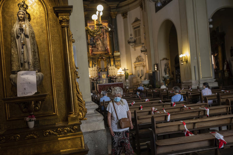 Catholic worshippers, wearing face masks protection to prevent the spread of the coronavirus, attend a mass at the San Ildefonso church in Madrid, Spain, Sunday, May 31, 2020. (AP Photo/Bernat Armangue)