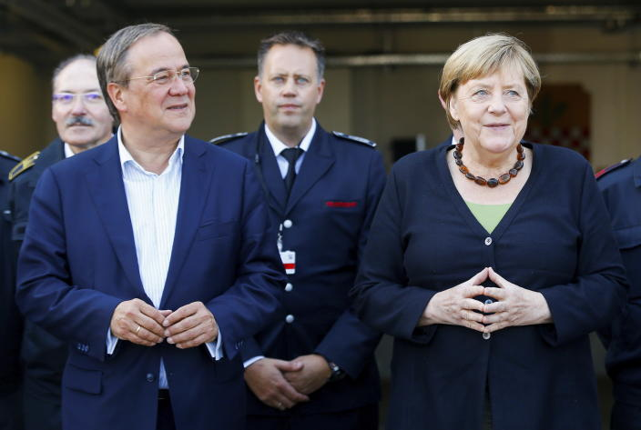 German Chancellor Angela Merkel and North Rhine-Westphalia's State Premier, chairman of the Christian Democratic Union party and candidate for Chancellery Armin Laschet, left, visit the fire station in Schalksmuehle, Germany, Sunday Sept. 5, 2021. (Thilo Schmuelgen/Pool via AP)