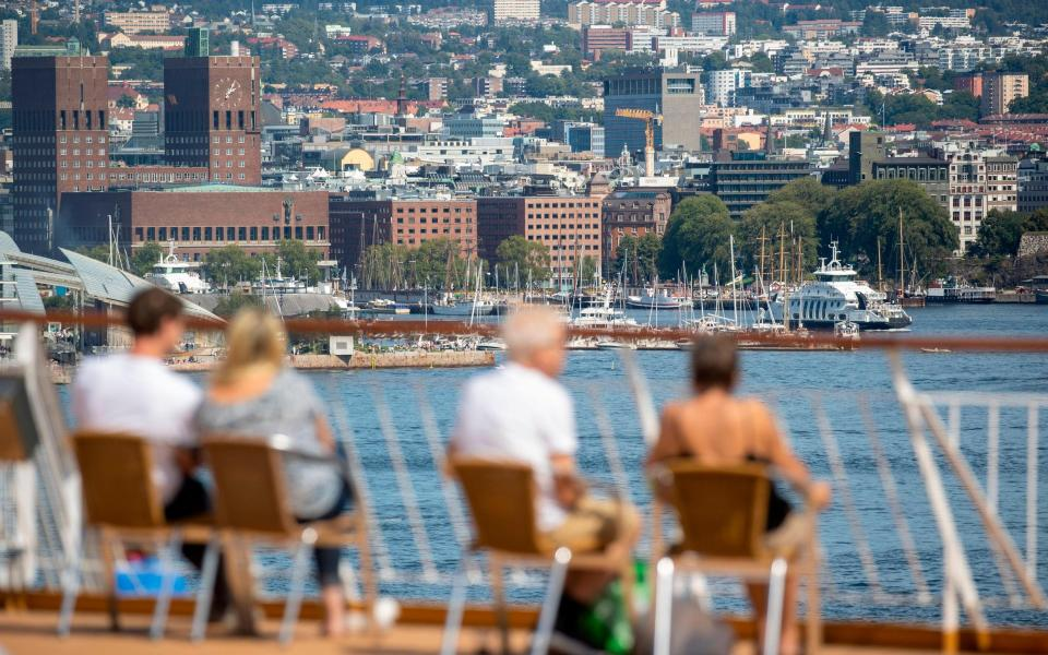 The Oslo town hall (L) is seen as people enjoy the view from a ferry in the Oslo fjord in the Norwegian capital - ODD ANDERSEN