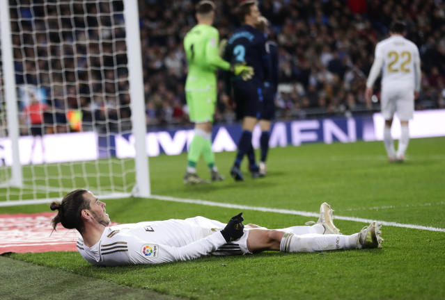 Real Madrid's Gareth Bale after falling off the playing area during the Spanish La Liga soccer match between Real Madrid and Real Sociedad at the Bernabeu stadium in Madrid, Spain, Spain, Saturday, Nov. 23, 2019. (AP Photo/Manu Fernandez)