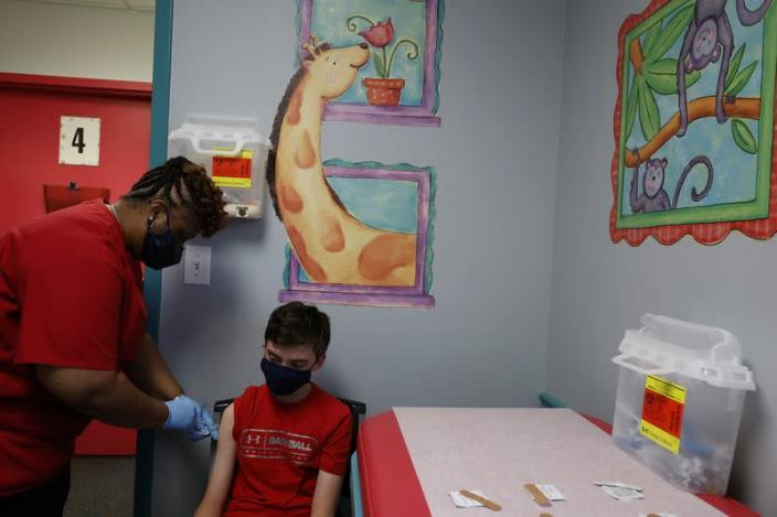 Aidan Mohl, 13, is inoculated with Pfizer's vaccine against coronavirus disease (COVID-19) by Registered Medical Assistant Melissa Dalton, after Georgia authorized the vaccine for ages over 12 years, at Dekalb Pediatric Center in Decatur