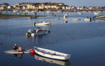 People sit on a paddle board floating in the Teign estuary taken from Shaldon, Devon, England looking across to the holiday resort of Teignmouth, Monday July 19, 2021. (AP Photo/Tony Hicks)