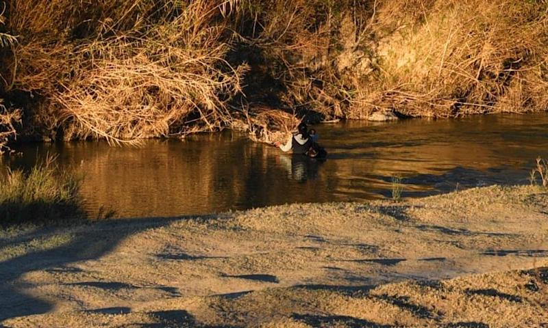 A woman crosses the Rio Bravo with a baby on her arms trying to reach the US city of Presidio on 20 February 2017.
