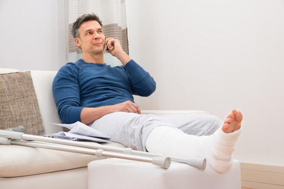 A man with a broken leg sitting on a couch and talking on the phone.