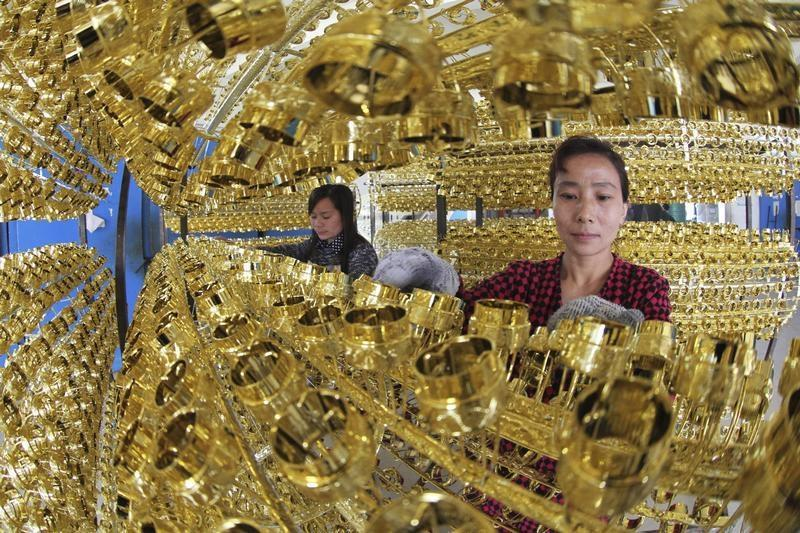 Employees work on the production line of a wine bottle cap factory in Ganyu county