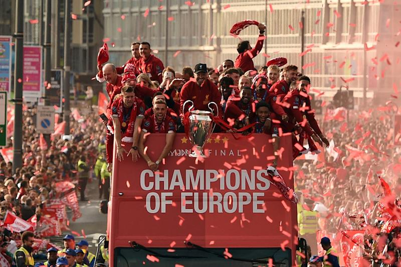 TOPSHOT - Liverpool's German manager Jurgen Klopp (C) holds the European Champion Clubs' Cup trophy during an open-top bus parade around Liverpool, north-west England on June 2, 2019, after winning the UEFA Champions League final football match between Liverpool and Tottenham. - Liverpool's celebrations stretched long into the night after they became six-time European champions with goals from Mohamed Salah and Divock Origi to beat Tottenham -- and the party was set to move to England on Sunday where tens of thousands of fans awaited the team's return. The 2-0 win in the sweltering Metropolitano Stadium delivered a first trophy in seven years for Liverpool, and -- finally -- a first win in seven finals for coach Jurgen Klopp. (Photo by Oli SCARFF / AFP) (Photo credit should read OLI SCARFF/AFP/Getty Images)