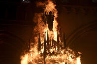 The statue of a saint is engulfed in flames after protesters torched the San Francisco de Borja church, a favorite of Chile's national police force, on the one-year anniversary of the start of anti-government mass protests over inequality in Santiago, Chile, Sunday, Oct. 18, 2020. (AP Photo/Esteban Felix)
