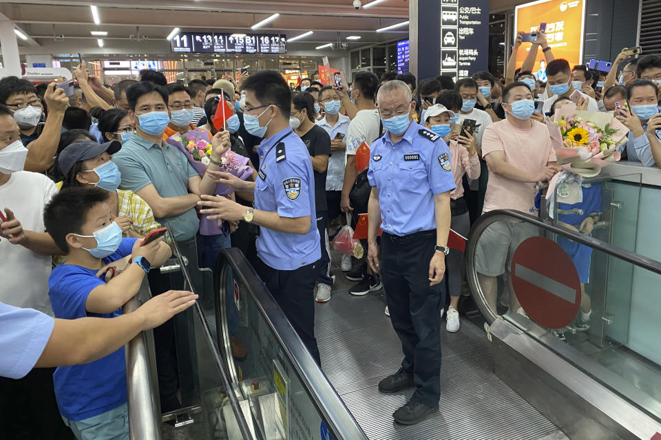 Police stand guard as supporters of Huawei CFO Meng Wanzhou gather at Shenzhen Bao'an International Airport in Shenzhen in southern China's Guangdong Province, Saturday, Sept. 25, 2021. China's government was eagerly anticipating the return of a top executive from global communications giant Huawei Technologies on Saturday following what amounted to a high-stakes prisoner swap with Canada and the U.S. (AP Photo/Ng Han Guan)