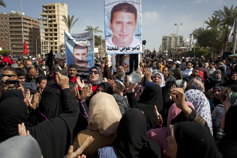 "Egyptian protesters chant anti-President Mohammed Morsi slogans and carry posters with pictures of victims of recent violence and their names in Port Said, Egypt, Friday, Feb. 22, 2013. In the restive city of Port Said, where a general strike entered its sixth day on Friday, factory workers, activists and laborers have held street rallies that brought the coastal city on the northern tip of the Suez Canal to a halt, though shipping in the international waterway has not been affected. Arabic on posters reads, ""the martyr of treachery, Tamer Awad el-Fahleh, Abdo el-Dosouk."" (AP Photo/Nasser Nasser)"