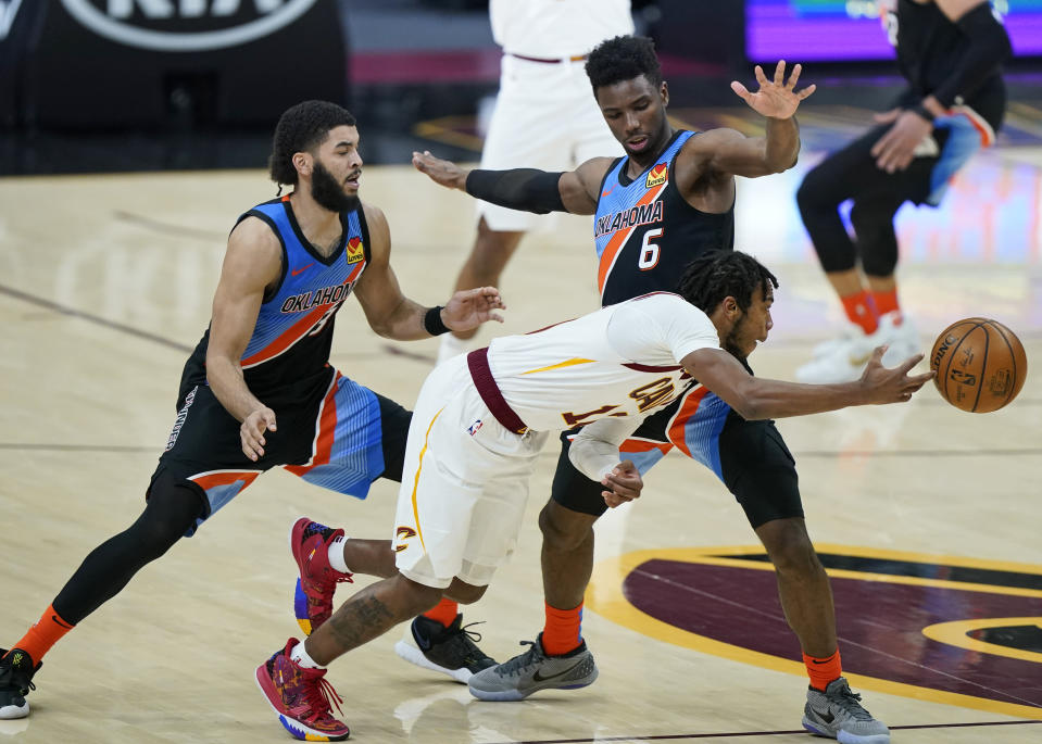 Cleveland Cavaliers' Darius Garland, front, passes against Oklahoma City Thunder's Hamidou Diallo, right, as Kenrich Williams, left, defends in the second half of an NBA basketball game, Sunday, Feb. 21, 2021, in Cleveland. (AP Photo/Tony Dejak)
