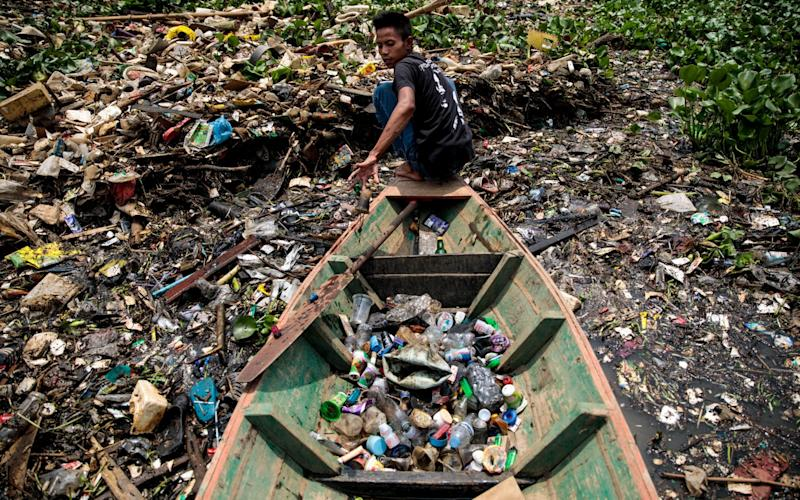 Rudiana, 24 from Cihampelos Village, collecting plastic in 2019 at the Saguling reservoir on the headwater of the Citarum river in Bandung, Java, Indonesia. The Citarum is considered one of the most polluted in the world and the Indonesian Army has been tasked with cleaning it up as part of an ambitious 7 year project - Jack Taylor
