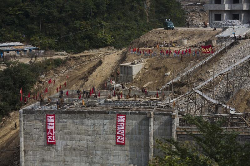 """In this Friday Sept. 20, 2013 photo, North Korean soldiers work at building project to construct a ski resort at North Korea's Masik Pass. The signs hanging from the unfinished wall, from left to right, read """"All Out Battle"""" and """"All Out Aggressive War."""" North Korean authorities have been encouraging a broader interest in sports and recreation in the country, calling it """"the hot wind of sports blowing through Korea."""" (AP Photo/David Guttenfelder)"""