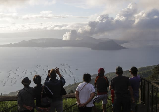 People look from Tagaytay, Cavite province, south of Manila, as Taal Volcano continues to spew ash (Aaron Favila/AP)