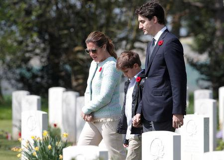 Canadian Prime Minister Justin Trudeau, his wife Sophie Gregoire and son Xavier walk past gravestones during their visit at the Canadian War Cemetery in Beny-sur-Mer