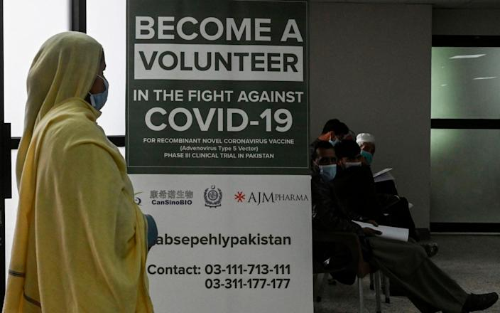 Volunteers wait to be given the jab at a hospital in Islamabad - AFP