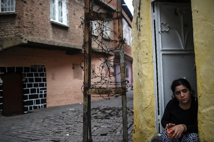 A woman sits at the entrance of her house in the district of Sur in Diyarbakir, southeastern Turkey, on October 31, 2015 on the eve of the country's general election (AFP Photo/Bulent Kilic)