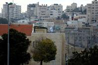 A building can be seen in the Israeli settlement of Maale Edumim, in the occupied West Bank, in the background the Palestinian village of Azariya is seen on the edge of Jerusalem, December 24, 2016. REUTERS/Amir Cohen