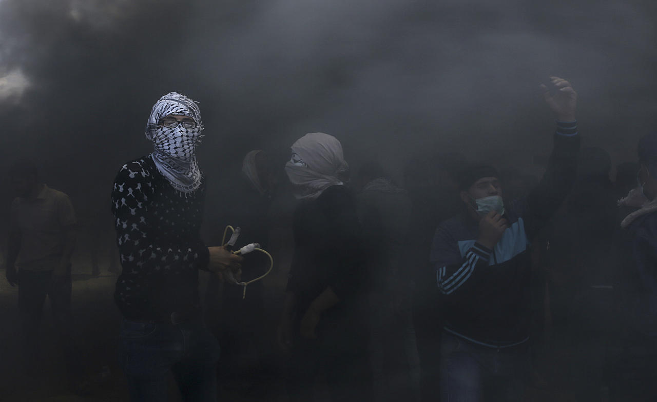 <p>Palestinian protesters hurl stones at Israeli troops while engulfed in smoke from burning tires near the Gaza Strip's border with Israel, east of Khan Younis, May 14, 2018. (Photo: Adel Hana/AP) </p>