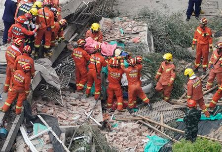 Firefighters carry a casualty on a stretcher at the site where a building collapsed, in Shanghai, China May 16, 2019. REUTERS/Aly Song