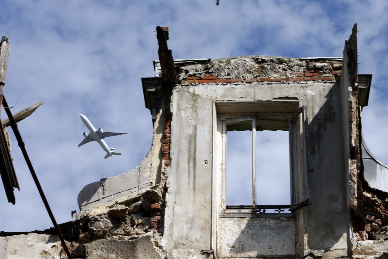 A commercial airliner flies over an abandoned 19th century manor in Goussainville-Vieux Pays, 20 kms (12 miles) north of Paris September 9, 2013. In 1972 the farming village of 144 homes found itself under the direct flight path of Roissy's Charles de Gaulle Airport when it opened. Residents started to abandon their homes, unable to endure the constant noise of the passenger planes flying overhead. Nowadays, only few families remain living in what has become almost a ghost village. Picture taken September 9, 2013. REUTERS/Charles Platiau (FRANCE - Tags: SOCIETY TRANSPORT)