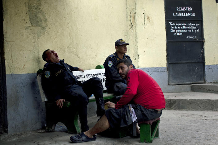 In this May 2, 2012 photo, a prison guard yawns as he gets his shoes shined at the San Pedro Sula Central Corrections Facility in San Pedro Sula, Honduras. Inside one of Honduras' most dangerous and overcrowded prisons, inmates operate a free-market bazaar, selling everything from iPhones to prostitutes. Guards do not cross into the inner sanctum controlled by prisoners, and prisoners do not breach the perimeter controlled by guards. (AP Photo/Rodrigo Abd)