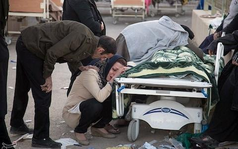Mourners gather around the body of one of the victims - Credit: Reuters