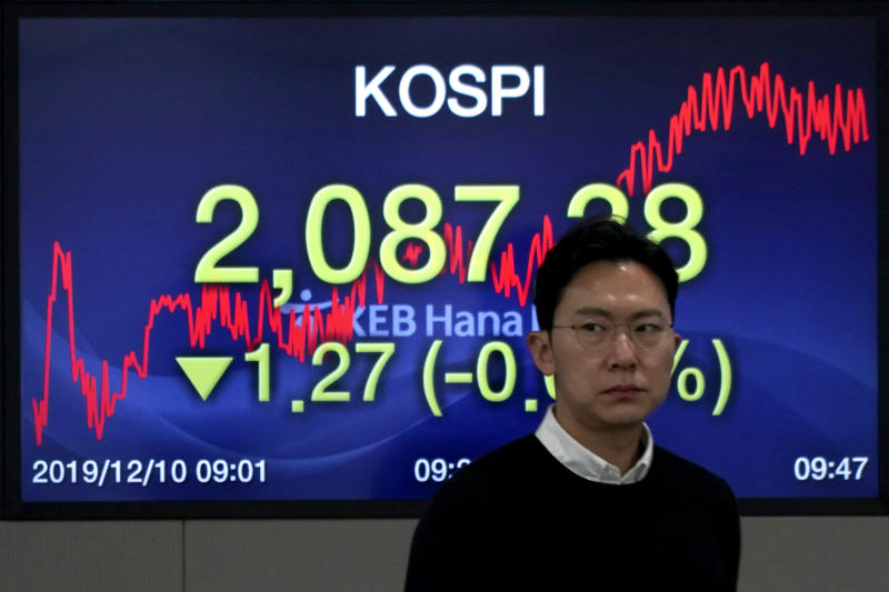 A currency trader walks by the screen showing the Korea Composite Stock Price Index (KOSPI) at the foreign exchange dealing room in Seoul, South Korea, Tuesday, Dec. 10, 2019. Asian stock markets have fallen as investors look ahead to interest rate decisions by U.S. and European central bankers and possible American tariff hike on Chinese imports.  (AP Photo/Lee Jin-man)