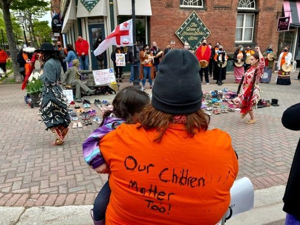 Indigenous community members organized an event with 215 pairs of childrens' shoes at the feet of the controversial John A. Macdonald statue Monday morning.