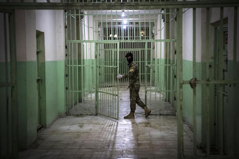 A member of the Syrian Democratic Forces (SDF) stands guard in a prison where men suspected to be affiliated with the Islamic State (IS) group are jailed in northeast Syria in the city of Hasakeh: Getty