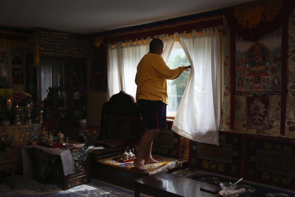 Jalue Dorje, 14, looks out the window for his father as they clean up after a weekend of ceremonies paying homage to Guru Rinpoche, the Indian Buddhist master who brought Tantric Buddhism to Tibet, on Tuesday, July 20, 2021, in Columbia Heights, Minn. (AP Photo/Jessie Wardarski)