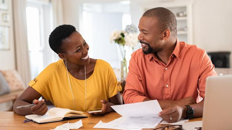 Cheerful mature couple sitting and managing expenses at home.
