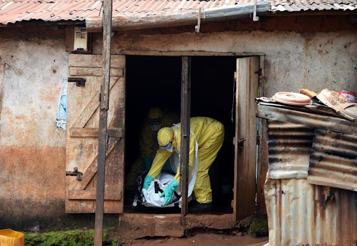 Health workers prepare to carry a corpse out of a house in Freetown, Sierra Leone, on November 12, 2014 (AFP Photo/Francisco Leong)