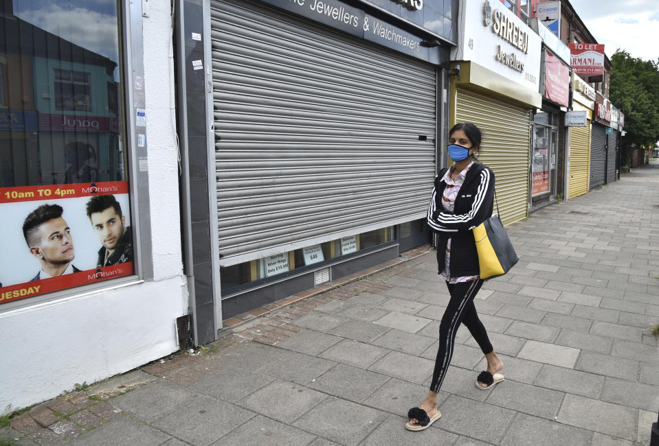 A woman wearing a mask to protect against coronavirus, walks in Melton Road also known as the Golden Mile in Leicester, England, Tuesday June 30, 2020. The British government has reimposed lockdown restrictions in the English city of Leicester after a spike in coronavirus infections, including the closure of shops that don't sell essential goods and schools. (AP Photo/Rui Vieira)