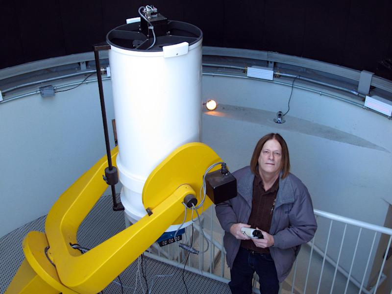 In this Feb. 25, 2012, photo, astronomy professor Daniel Caton poses for a photo with a low-light video camera at the campus observatory at Appalachian State University in Boone, N.C. Caton is hoping to use the cameras to capture a phenomenon known as the Brown Mountain lights. (AP Photo/Allen Breed)