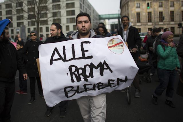 """BERLIN, GERMANY - APRIL 08: A man holds a banner with the written slogan """"Alle Roma Bleiben"""" (All Roma Stay) as ethnic Roma protest against discrimination against Roma on International Roma Day on April 8, 2013 in Berlin, Germany. Western Europe has experienced a large influx of Roma, who are also called Gypsies, from Romania and Bulgaria in recent years following the accession of the two countries to the European Union. Restrictions on the rights of Romanian and Bulgarian citizens to work in the EU are scheduled to end at the end of 2013. (Photo by Carsten Koall/Getty Images)"""