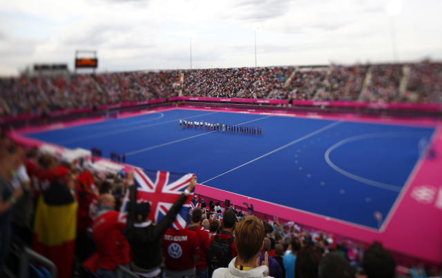 Britain and Argentina players line up before their men's Group A hockey match at the London 2012 Olympic Games at the Riverbank Arena on the Olympic Park in London July 30, 2012. Picture taken with a tilt-shift lens. REUTERS/Kai Pfaffenbach (BRITAIN - Tags: SPORT OLYMPICS SPORT FIELD HOCKEY)
