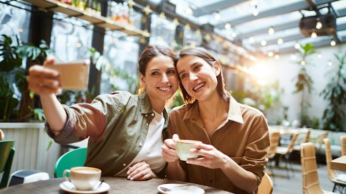 Happy attractive young women in casual shirts sitting at table in coffee shop and photographing together while drinking coffee.
