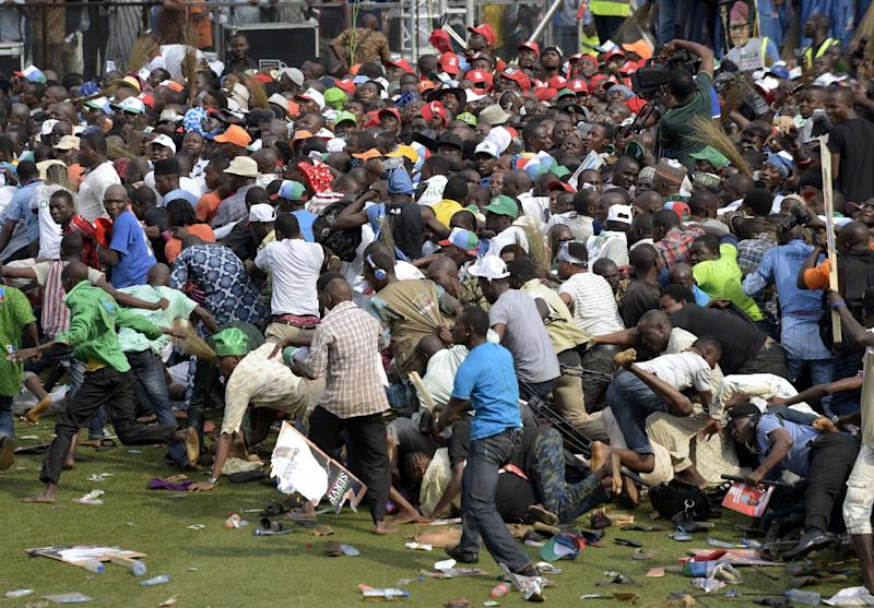 People fall as they run for safety after violence broke out during a presidential campaign rally of Nigeria's main opposition All Progressives Congress (APC) at Taslim Balogun Stadium in Lagos on January 30, 2015 (AFP Photo/Pius Utomi Ekpei)