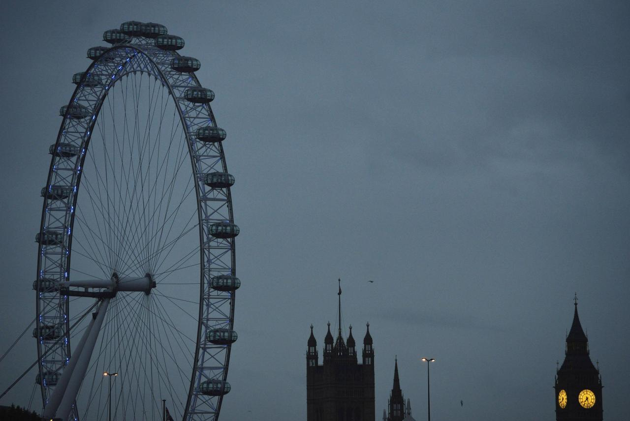The London Eye is seen near the Houses of Parliament at dawn in central London October 21, 2013. Merlin Entertainments, whose attractions include the Madame Tussauds waxworks and Legoland theme parks, plans to sell at least 20 percent of its shares in a stock market debut in London. REUTERS/Toby Melville (BRITAIN - Tags: ENTERTAINMENT SOCIETY BUSINESS)