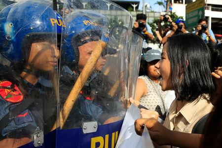 A protester confronts anti-riot police officers during a protest against U.S. President Trump's visit in Manila
