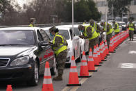 Members of the National Guard help motorists check in at a federally-run COVID-19 vaccination site set up on the campus of California State University of Los Angeles in Los Angeles, Tuesday, Feb. 16, 2021. (AP Photo/Jae C. Hong)
