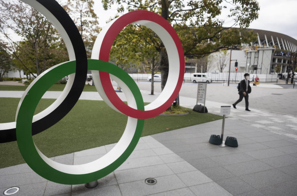 A man walks by a part of Olympic rings displayed at the Japan Olympic Museum situated across from the Japan National Stadium planned to be used for the postponed Tokyo 2020 Olympic Games in Tokyo Friday, April 2, 2021. Many preparations are still up in the air as organizers try to figure out how to hold the postponed games in the middle of a pandemic. (AP Photo/Hiro Komae)