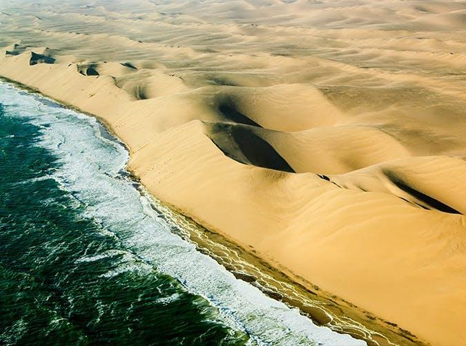 <p>Dotted with shipwrecks and whale bones, Namibia's Skeleton Coast is a graveyard of sorts. But the barren stretch of land, where green sea meets sand dunes, is so stark it's an eerie type of beautiful.</p>