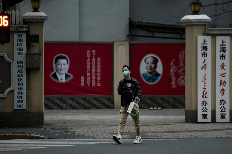 Image: A man wearing a mask walks by portraits of Chinese President Xi Jinping and late Chinese chairman Mao Zedong as the country is hit by an outbreak of the novel coronavirus, on a street in Shanghai