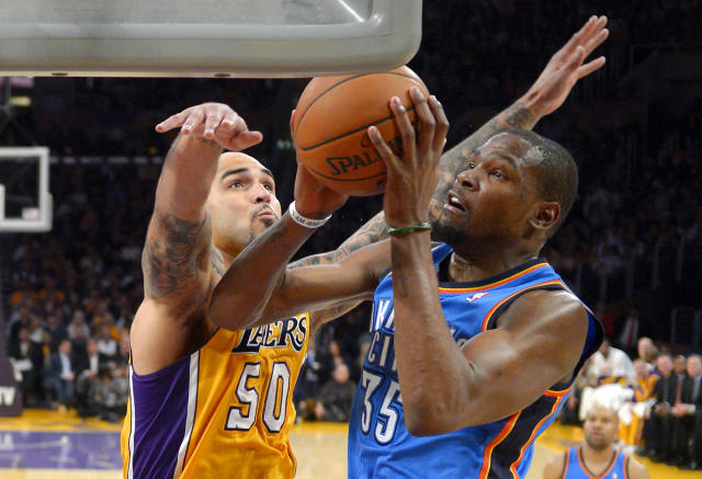 Oklahoma City Thunder forward Kevin Durant, right, puts up a shot as Los Angeles Lakers center Robert Sacre defends during the first half of an NBA basketball game Thursday, Feb. 13, 2014, in Los Angeles. (AP Photo/Mark J. Terrill)