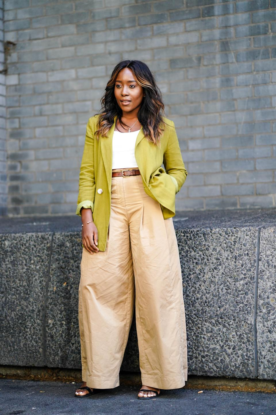 A guest is seen wearing a green khaki blazer jacket and flared beige trousers. [Photo: Getty]