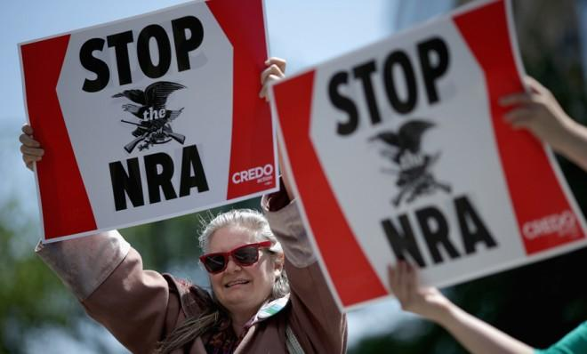 Anti-gun violence demonstrators hold signs condemning the National Rifle Association in Washington, D.C., on April 25.