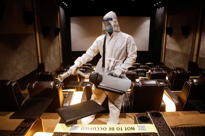A man in personal protective equipment sanitizes a cinema hall before a movie amid the spread of the coronavirus disease (COVID-19) in Mumbai