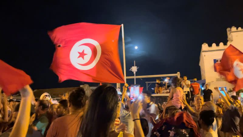 People react in the street after Tunisia's president dismissed government and froze parliament, in La Marsa